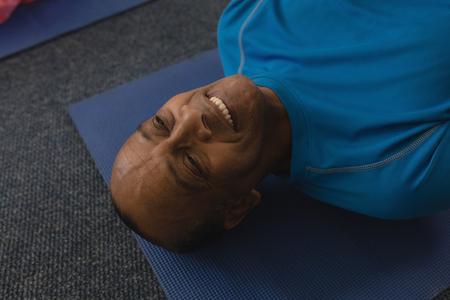 Close-up of happy senior man exercising on yoga mat in fitness studio