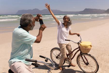 Vista lateral del hombre mayor haciendo clic en la foto de la mujer mayor con teléfono móvil en la playa bajo el sol con montañas al fondo
