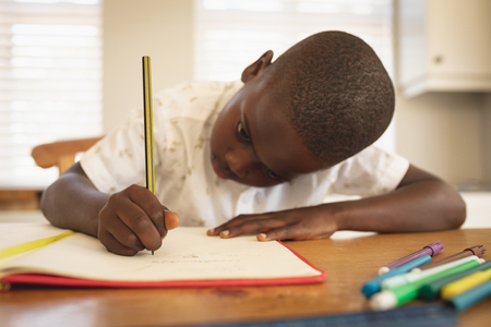 Close-up African American boy doing homework on dining table in kitchen at home