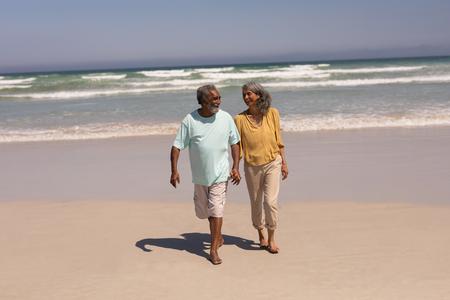 Vista frontal de la feliz pareja senior cogidos de la mano y caminar en la playa bajo el sol