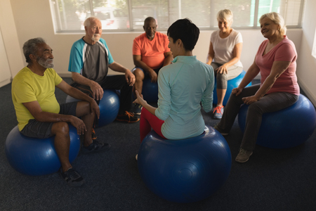 Front view of female trainer training senior people in performing exercise on ball at home