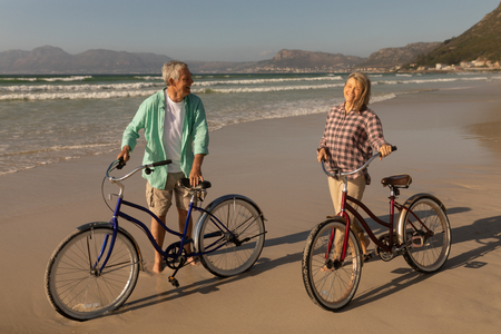 Front view of active senior couple standing with bicycle on the beach