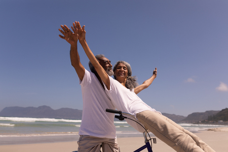 Low angle view of happy senior man rides a bicycle with senior woman sitting on handlebar at beach in the sunshine with mountains in the background Imagens