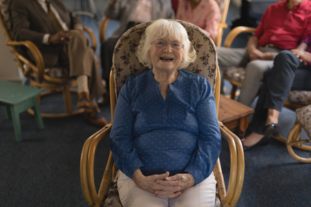 Front view of happy senior woman with hand clasped, sitting and looking at camera in nursing home Imagens