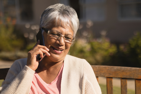 Close-up of active mixed-race senior woman talking on mobile phone in park on sunny day Stock Photo