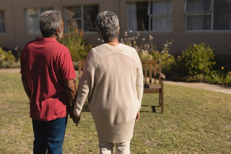 Rear view of senior couple standing hand in hand in the park of nursing home