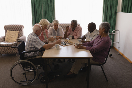 Front view of group of senior people playing chess on table in living room at home Imagens