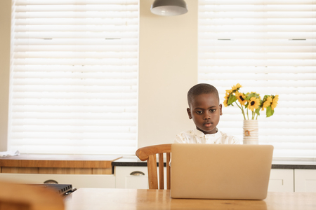 Front view of African American boy using laptop at dining table in kitchen at home