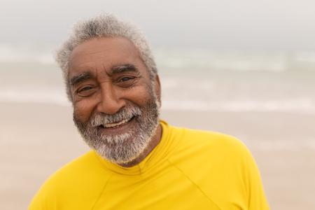 Close-up of happy senior man looking at camera on the beach Imagens