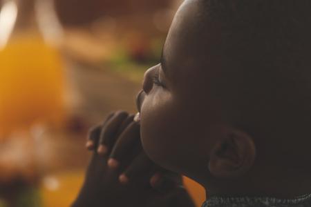 Primo piano di un ragazzo afroamericano con la mano stretta e gli occhi chiusi pregando al tavolo da pranzo a casa Archivio Fotografico