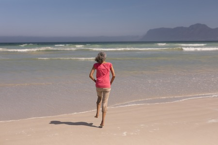 Rear view of senior woman running on beach in the sunshine Stock Photo