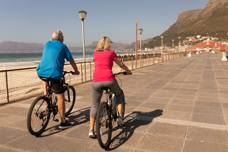 Rear view of senior couple riding a bicycle on a promenade at beach Stok Fotoğraf