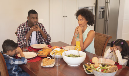 Front view of African American family with hands clasped and eyes closed praying together at dining table in a comfortable home Stock Photo