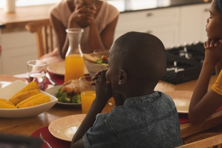 Rear view of African American family with hand clasped and eyes closed praying together at dining table at home