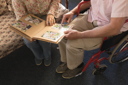 Low section of senior couple looking at photo album and showing a picture in living room at nursing home
