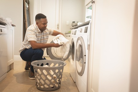 Side view of African American man washing clothes in washing machine at home Reklamní fotografie