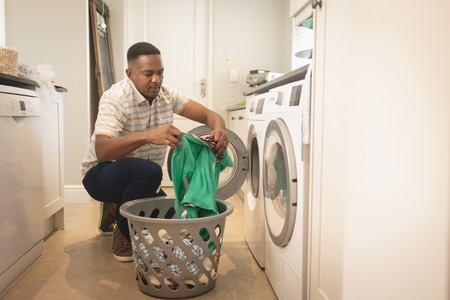Front view of African American man washing clothes in washing machine at home