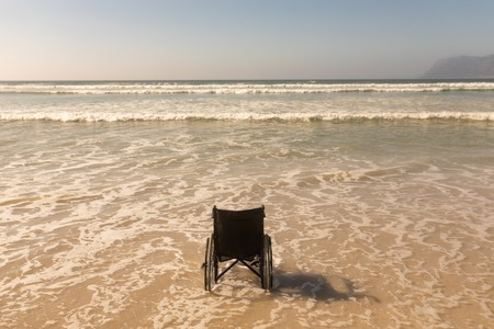 Rear view of empty wheelchair at seashore on the beach