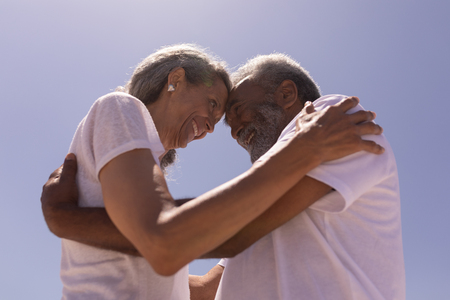 Low angle view of happy senior couple head to head and embracing each other on beach in the sunshine Stok Fotoğraf