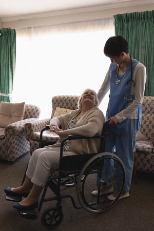 Front view of female doctor interacting with disabled senior woman on wheelchair in living room at home