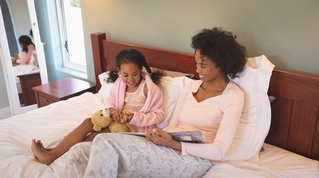 Happy African American mother and her cute daughter reading a book on bed in bedroom at home