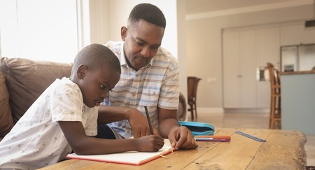 Side view of African American father helping his son with homework at table in a comfortable home Stock Photo
