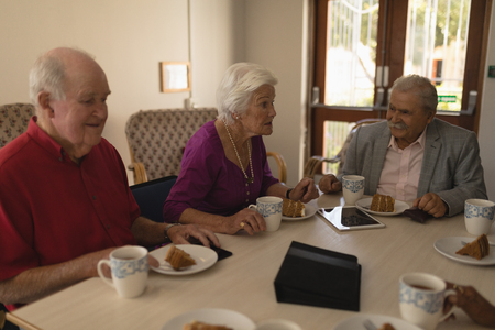 Front view of happy group of senior friends having breakfast on dining table at home