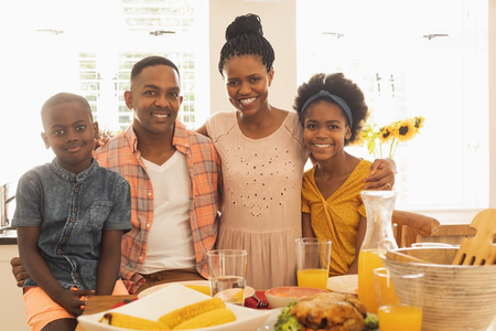 Portrait of happy African American family looking at camera in front of dining table in their comfortable home