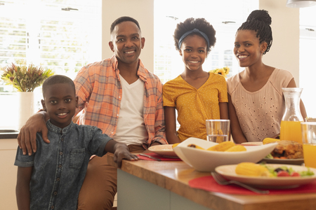 Portrait of happy African American family looking at camera at dining table in comfortable home