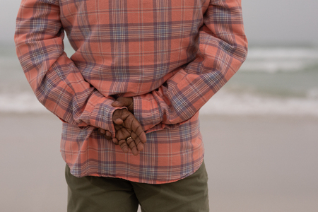 Mid section of senior man with hands behind back standing on the beach