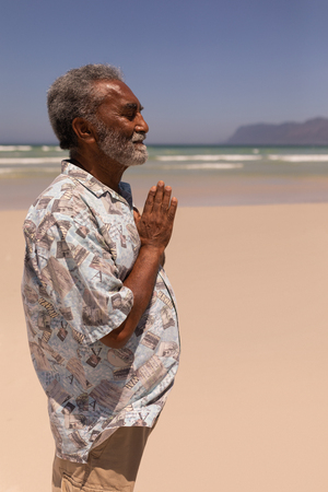 Side view of senior black man with hands clasped praying on beach in the sunshine Stock Photo