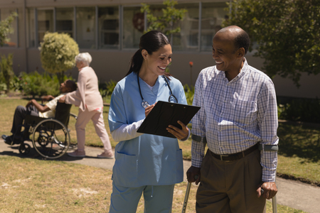 Front view of happy young female doctor discussing medical report with senior man on clipboard in garden