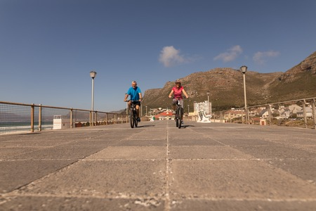 Low angle view of active senior couple riding a bicycle on a promenade at beach Stockfoto