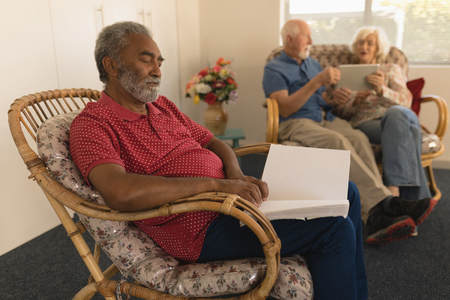 Side view of blind senior man reading a braille book on chair while senior couple using digital tablet at nursing home
