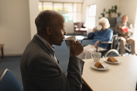 Side view of senior man drinking coffee in foreground with his friends behind him on dining table at home