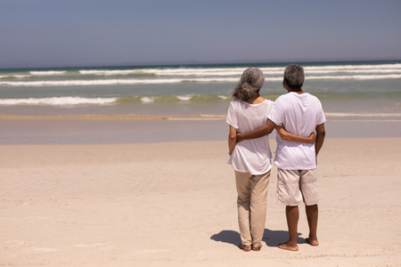 Rear view of senior couple standing on a beach with their arms around each other in the sunshine