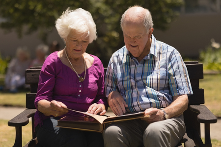 Front view of active senior couple concentrated looking at photo album while sitting on a benchin the park