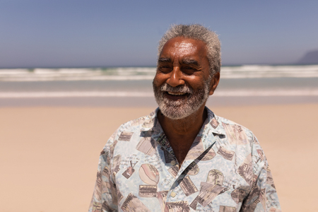 Front view of happy senior black man standing on beach in the sunshine Imagens - 121732905