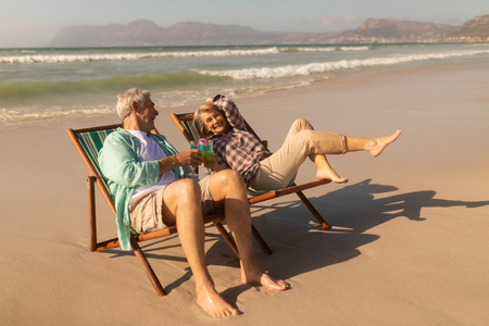 Side view of active senior couple having cocktail drink while relaxing on sun lounger at beach