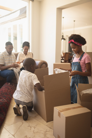 Side view of African American children unpacking their belongings and parents sitting on sofa at home Imagens