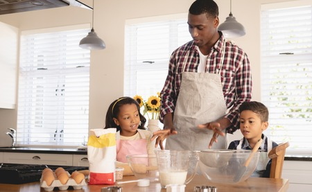 Front view of African American father and children baking cookies in kitchen at home