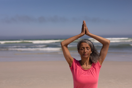 Front view of senior woman with eyes closed and hands clasped doing yoga on beach in the sunshine
