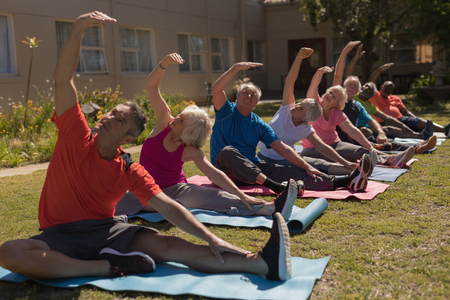 Front view of group of active senior people exercising aligned in the park. They are looking their hand Stockfoto