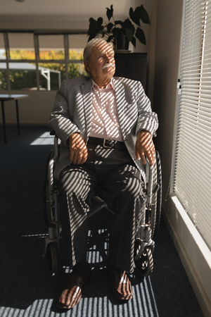 Front view of disable senior man sitting on wheelchair and looking outside through window at home