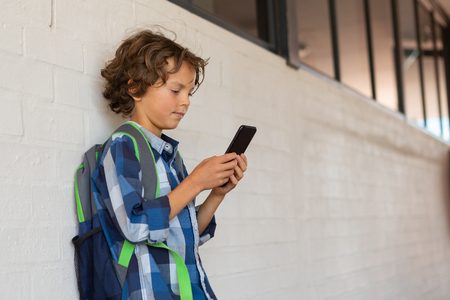Side view of a Caucasian schoolboy using his mobile phone while leaning against a wall in the corridor at school