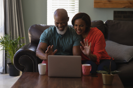 Front view of senior couple making video call on laptop in living room at home