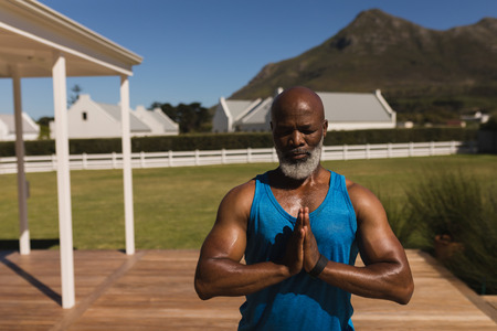 Front view of an active senior African American man performing yoga in the backyard of home