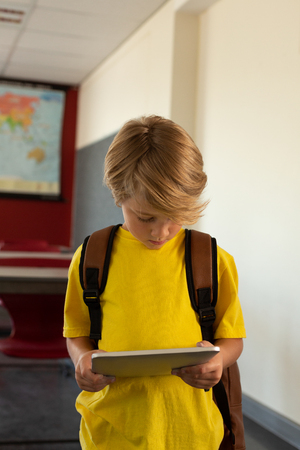 Front view of a cute Caucasian boy with school bag using digital tablet in a classroom at elementary school