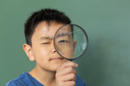 Front view of Asian schoolboy looking through magnifying glass against greenboard in a classroom at elementary school