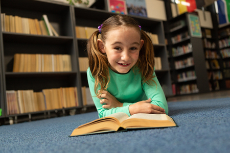 Front view of Caucasian smiling schoolgirl with book lying on floor and looking at camera in library at elementary school